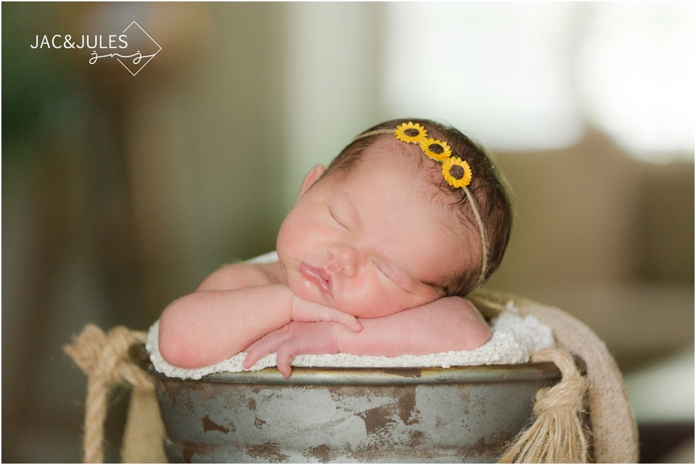 newborn baby girl in sunflower headband at home in middletown, nj