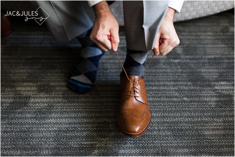 Groom tying his shoes at Courtyard Marriott in Wall, NJ