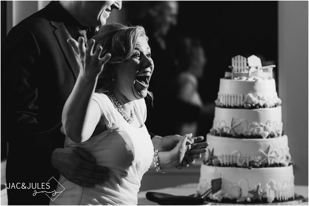 Bride's great expression during cake cutting at wedding reception in the ballroom at The Lobster Shanty in Point Pleasant, NJ.