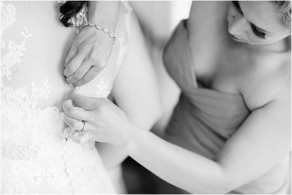 bride gets dressed with help from her maid of honor