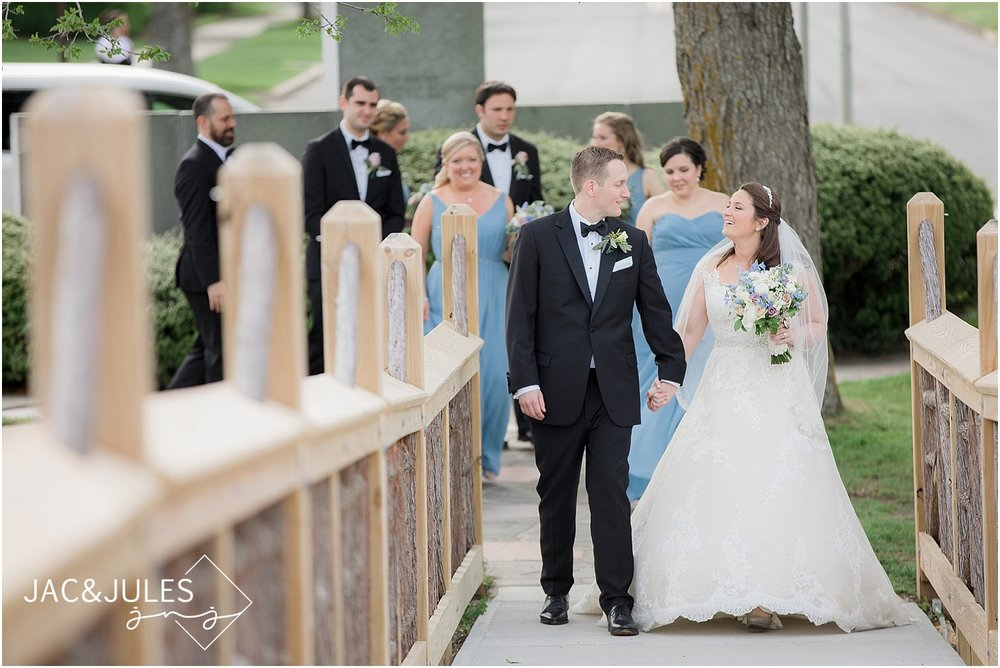 bride and groom walk the bridge at divine park in spring lake nj