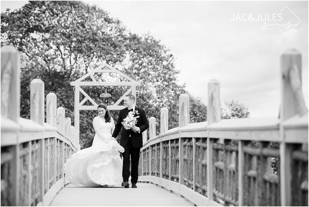 bride and groom take photos on the bridge in spring lake nj