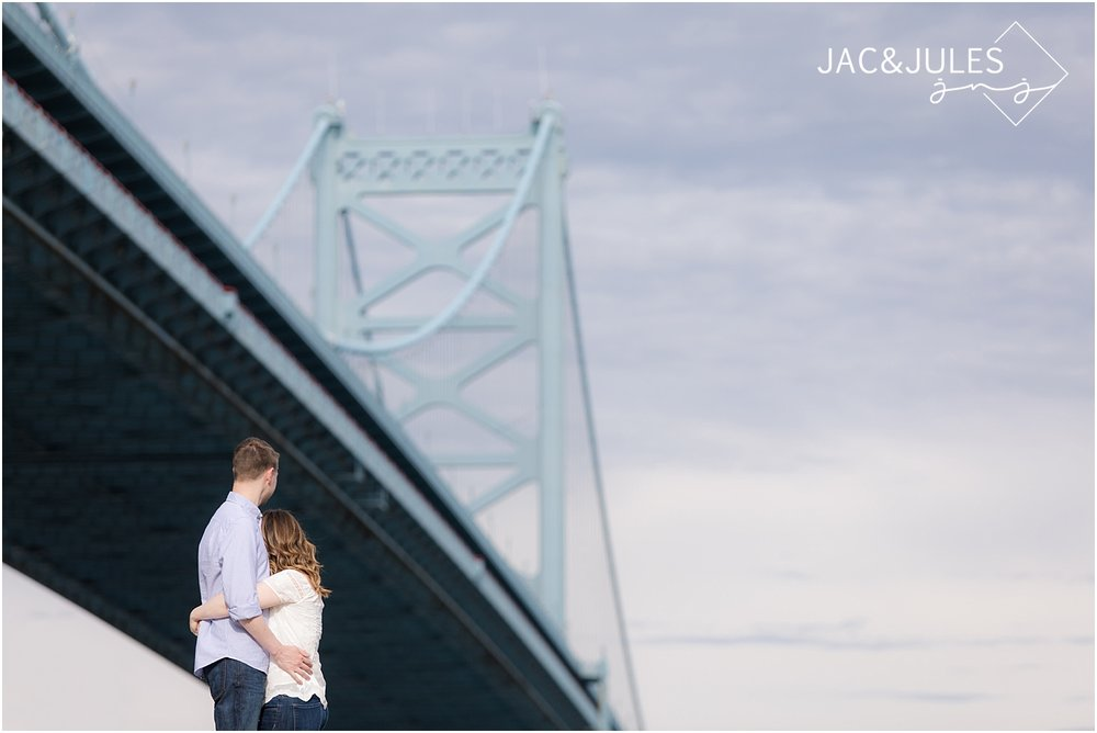 engagement photos under the ben franklin bridge in philadelphia