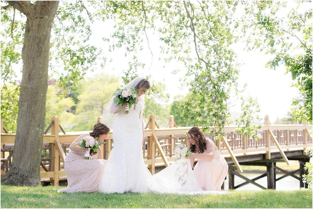 candid photo of bridesmaids fixing brides dress in spring lake nj