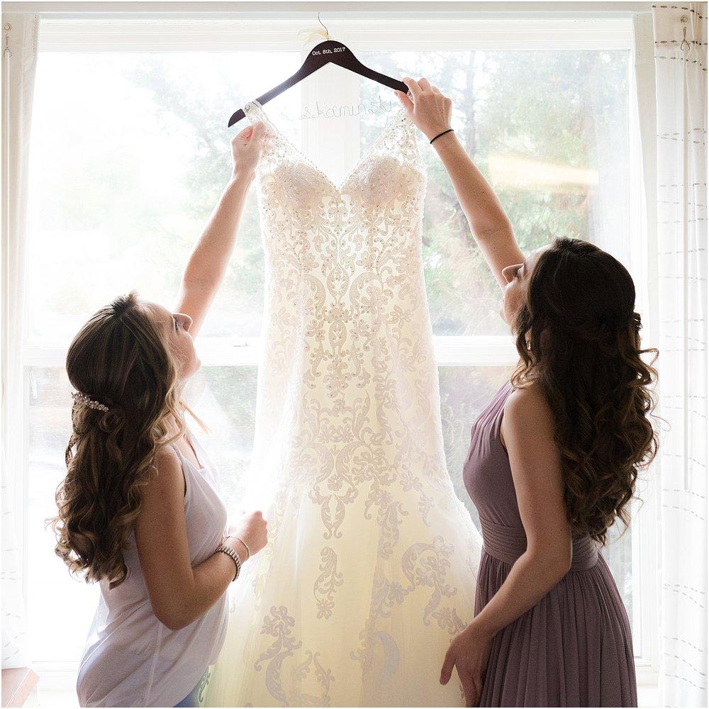 maid of honor helps bride get dressed