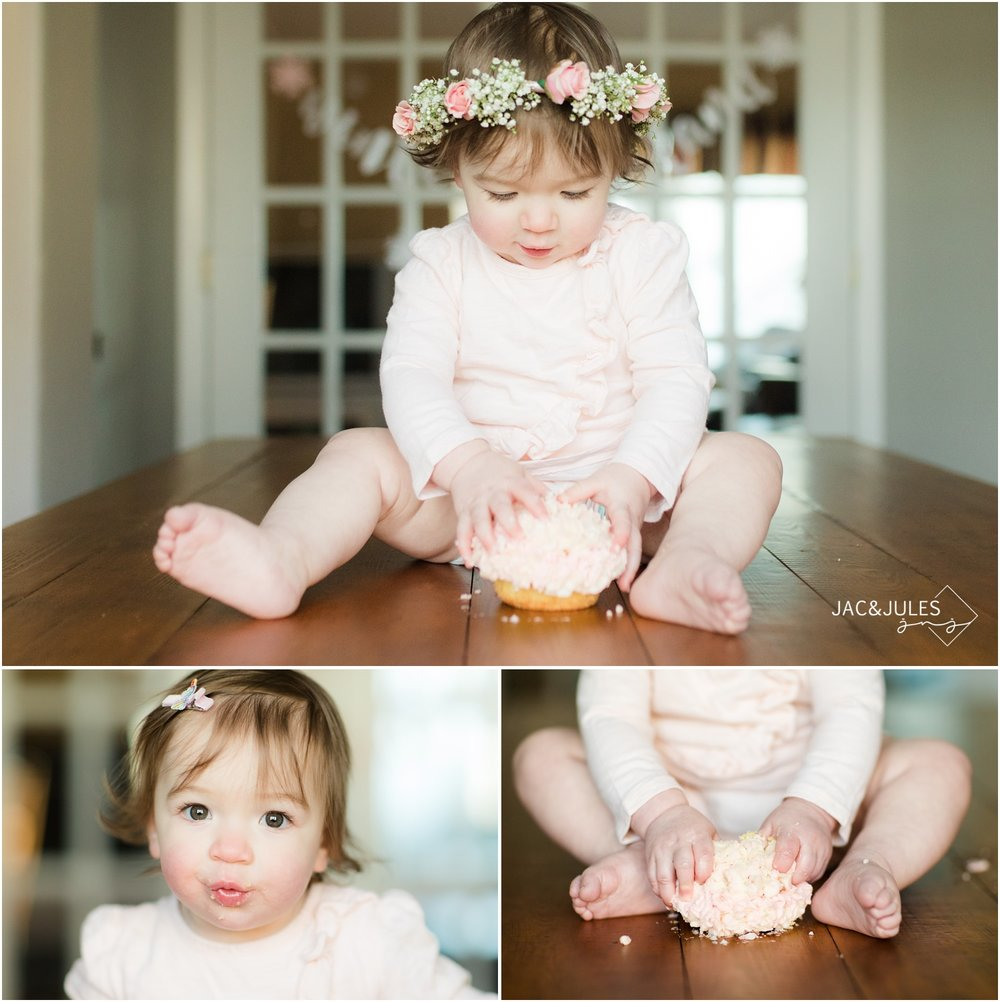 One year old girl wearing flower crown goes crazy smashing cake for first birthday.
