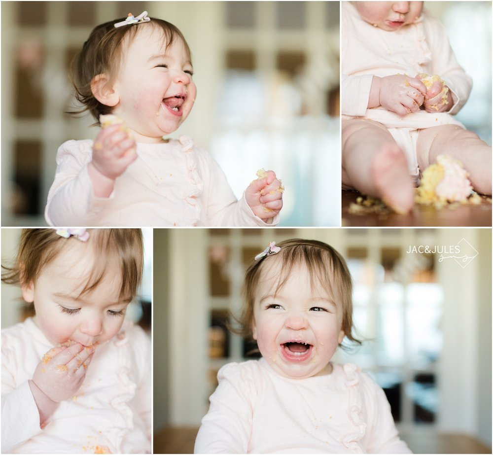 Super happy first birthday girl laughing during cake smash.