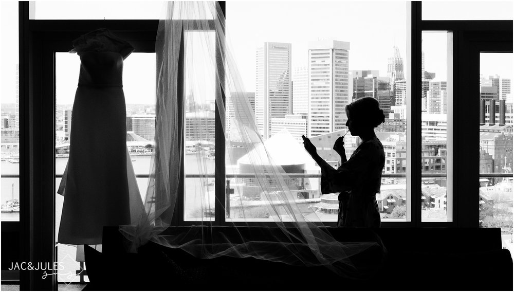silhouette photo of bride touching up make up with Baltimore skyline at The Four Seasons Hotel.