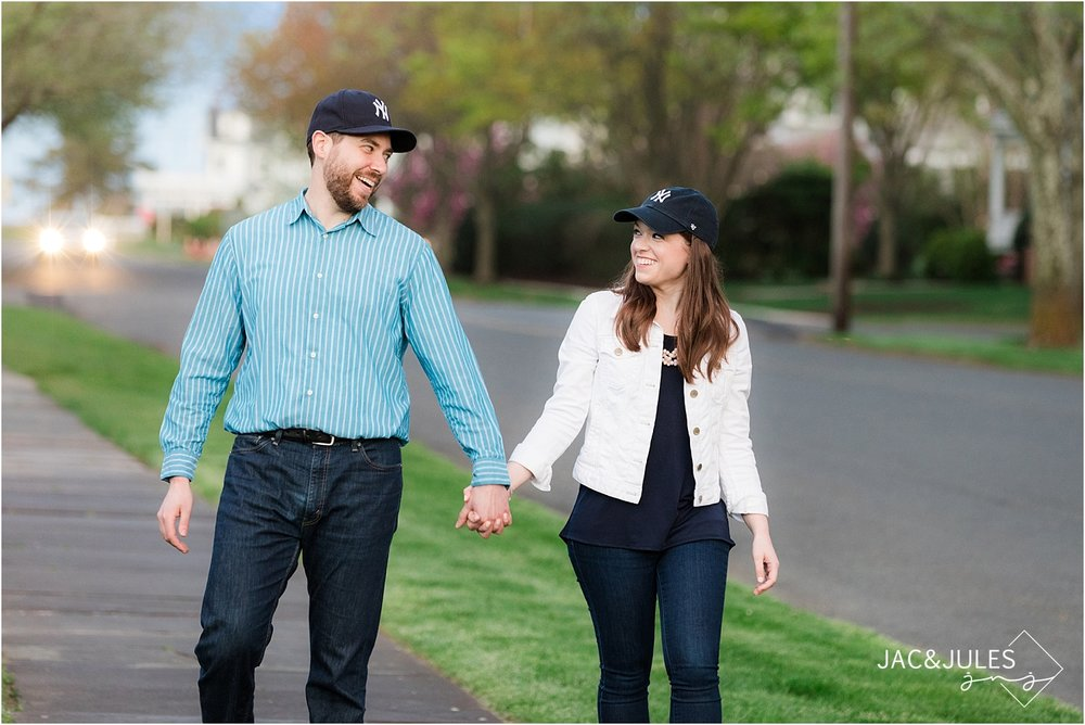 fun couple poses with yankee hats at their engagement session in spring lake nj