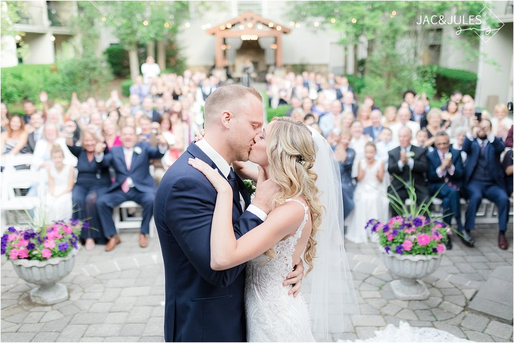 first kiss at ceremony in olde mill inn courtyard