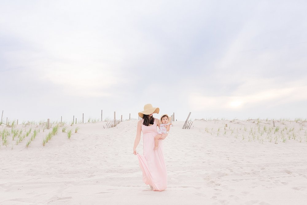 mom and daughter wearing dresses and sun hats walking on the beach in Island Beach State Park NJ