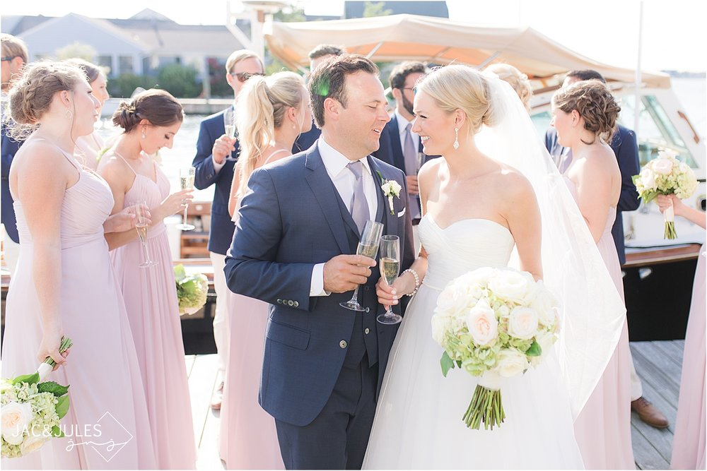 Natural light wedding photo of bride and groom and bridal party at bay head yacht club with a boat and cocktails