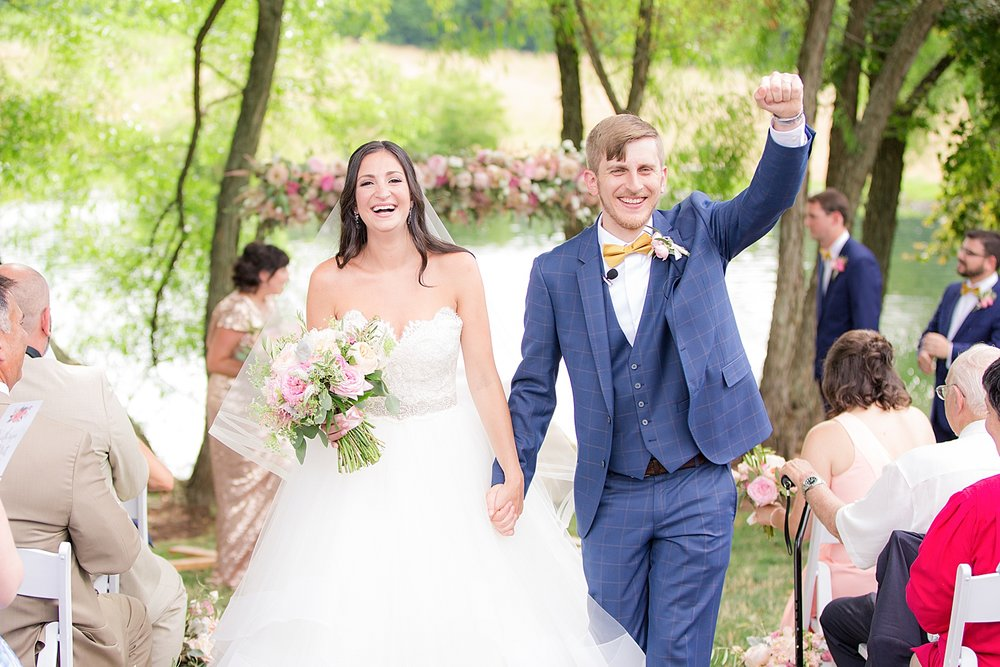 bride and groom walk down the aisle at the farm at eagles ridge in lancaster pa