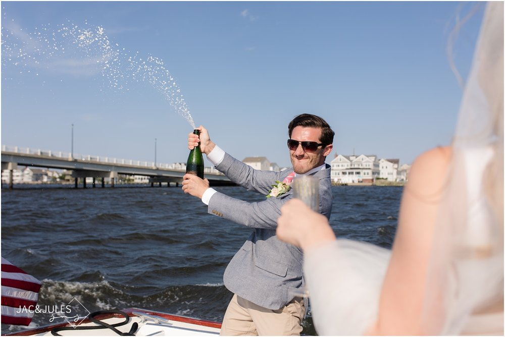 Groomsman popping champagne on a boat ride to Mantoloking Yacht Club to enter the wedding reception.