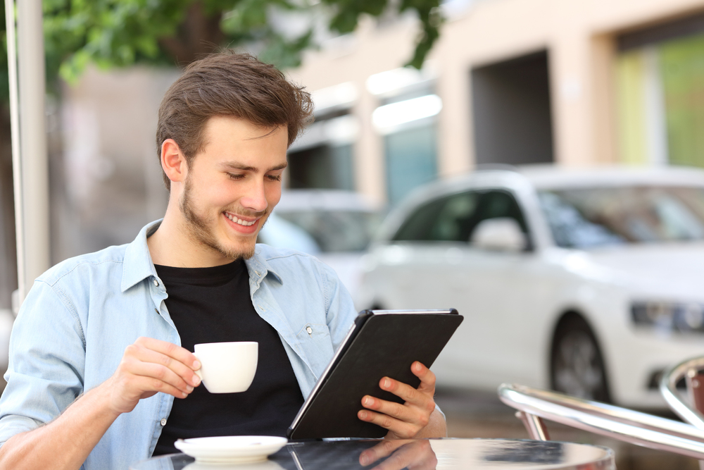 Bigstock_ 67667237 - Man Reading An Ebook Or Tablet In A Coffee Shop.jpg