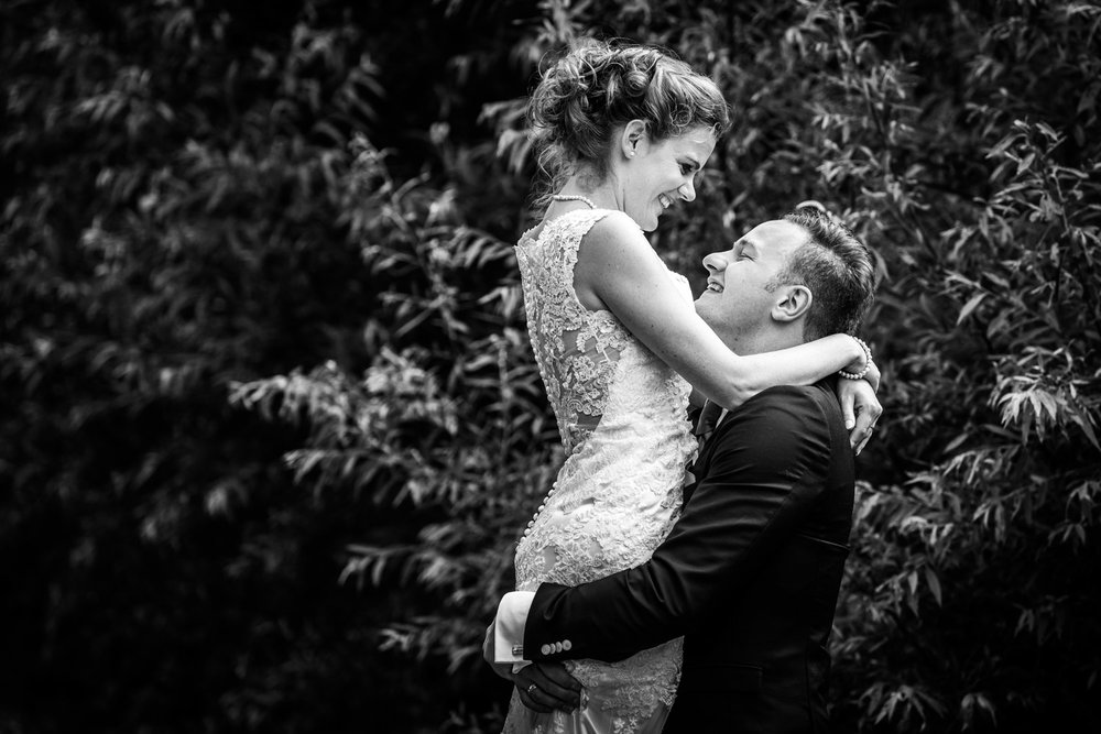 trouwfotograaf Cfoto, bij omhelzing bruidspaar, bruidegom tilt bruid op, trouwfotografie Rotterdam