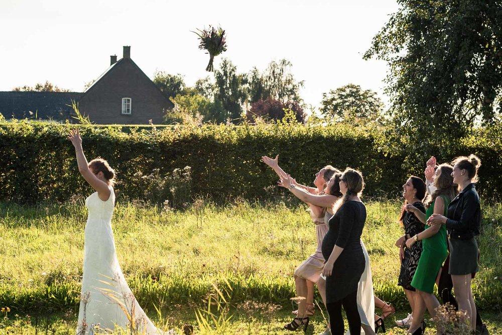Gooien van het bruidsboeket, door bruidsfotograaf Cfoto tijdens huwelijk op Benedensas