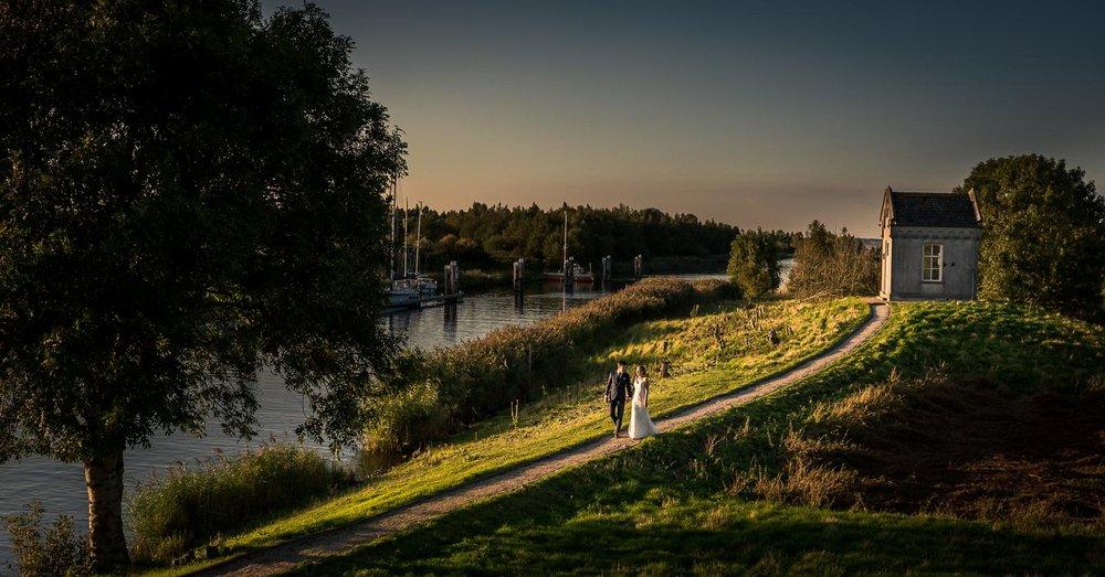 Bruidsfotograaf Cfoto maakte deze foto bij Benedensas met een oud kapelletje op de achtergrond, dicht bij het sluisje
