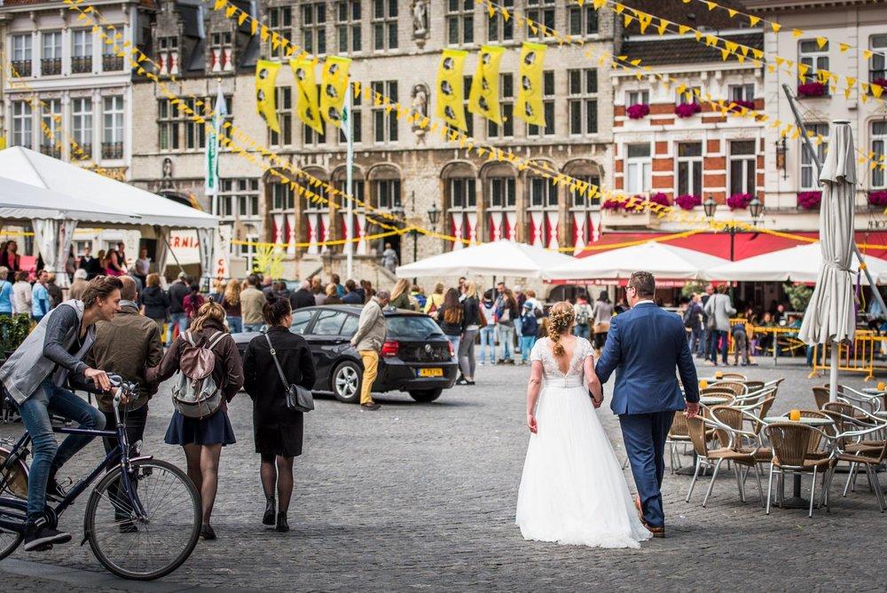 Copy of Copy of bruidspaar loopt over de grote markt in Bergen op Zoom, door trouwfotograaf Cfoto