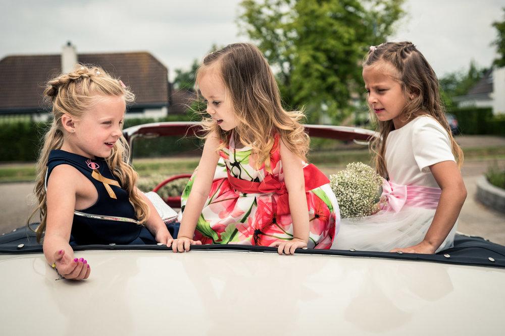 bruidskindjes spelen in de trouwauto in West Brabant door Caroline bruidsfotograaf bij Cfoto