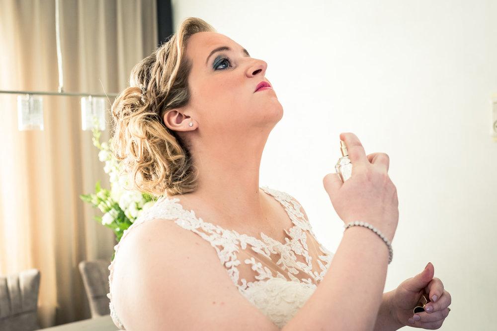 Tijdens de bruidsreportage spuit de bruid parfum op bij het aank
