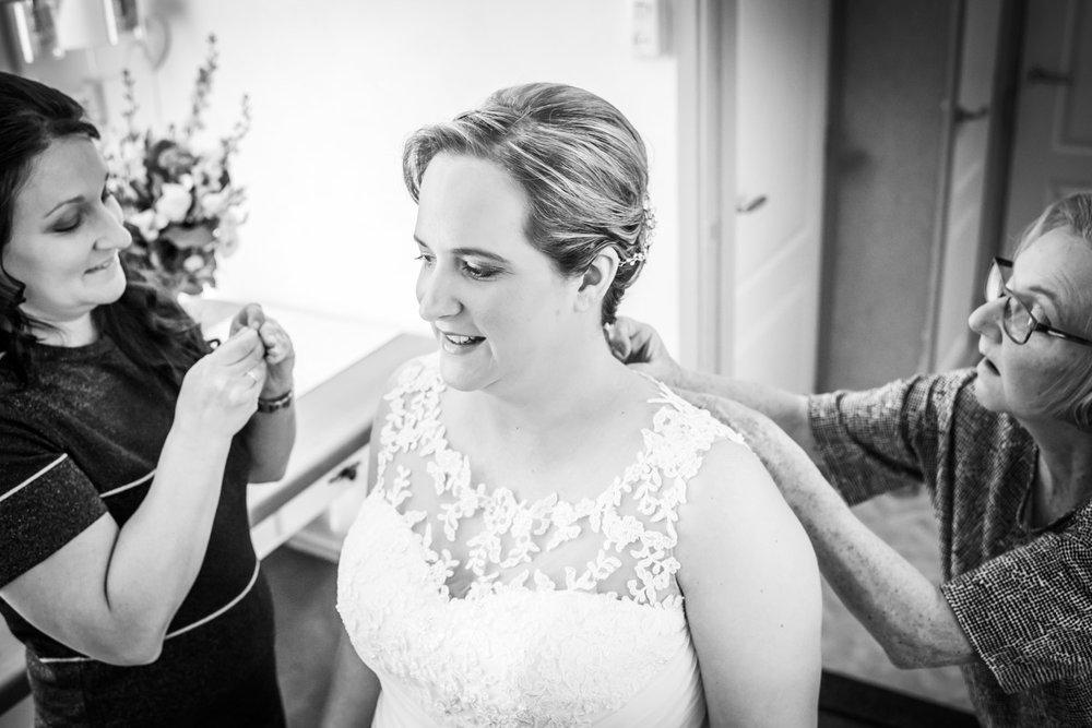 De sierraden worden aangedaan bij het aankleden, bruidsfotografi