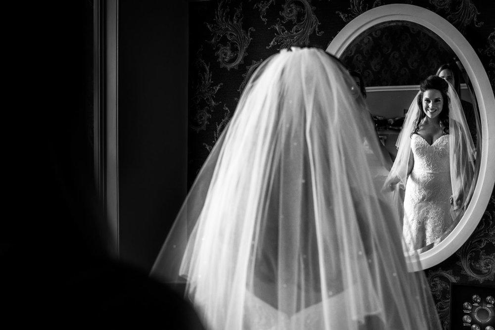 Bruidsfotografie in Breda de bruid bekijkt zichzelf tijden het a