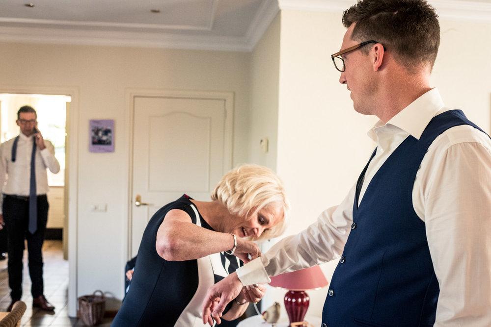 In de ochtend helpt de moeder van den bruidegom bij aankleden fo