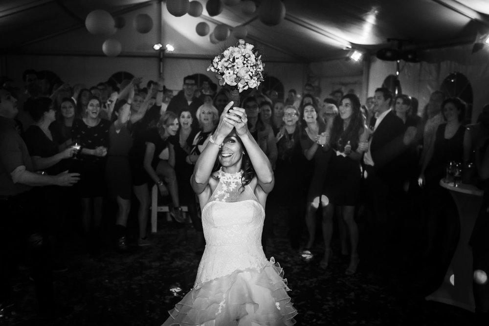 Huwelijksfotograaf legt vast het gooien van het boeket tijdens h