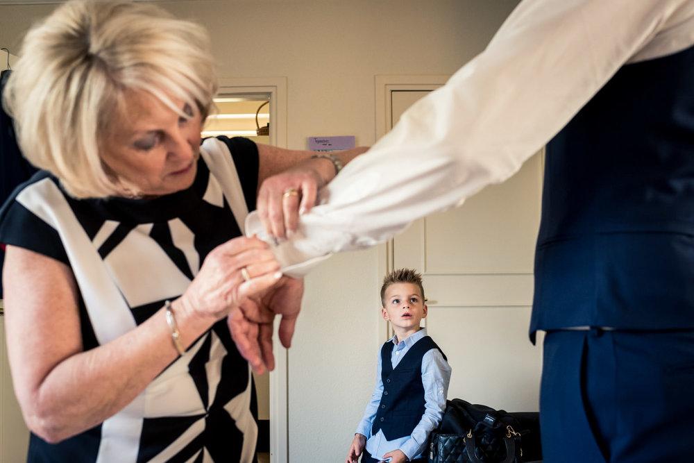 Cfoto legt vast als de moeder helpt de bruidegom bij aankleden,