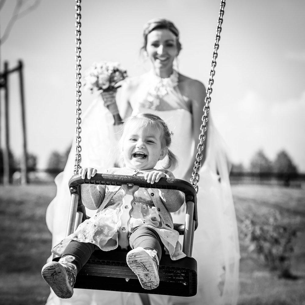 Bruid met bruidskindje in de speeltuin tijden de bruidsreportage