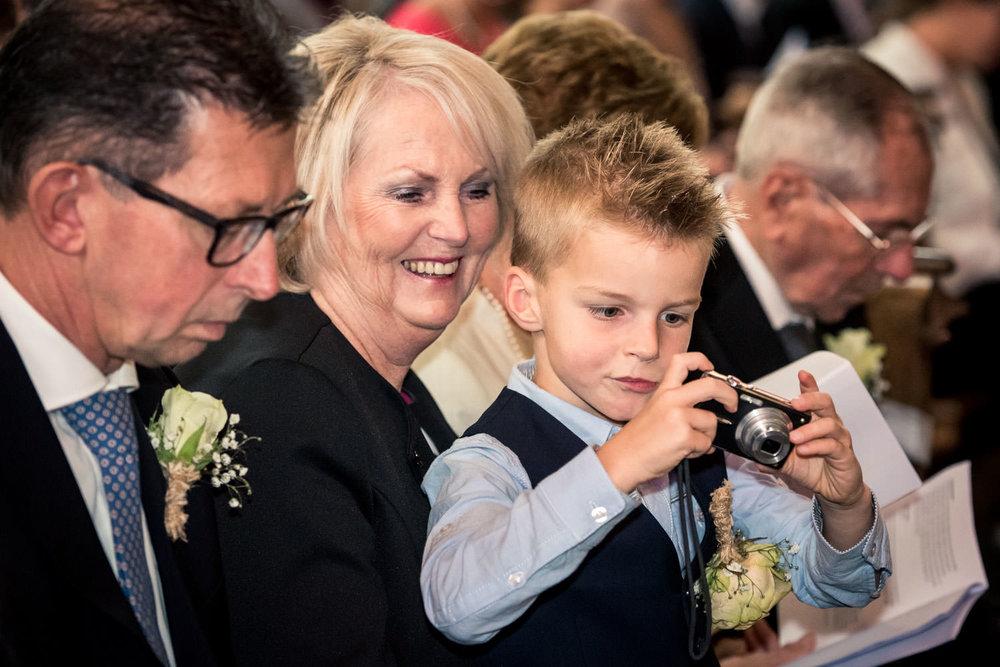 Een bruidsjonkertje maakt een foto tijdens de ceremonie, mooie h