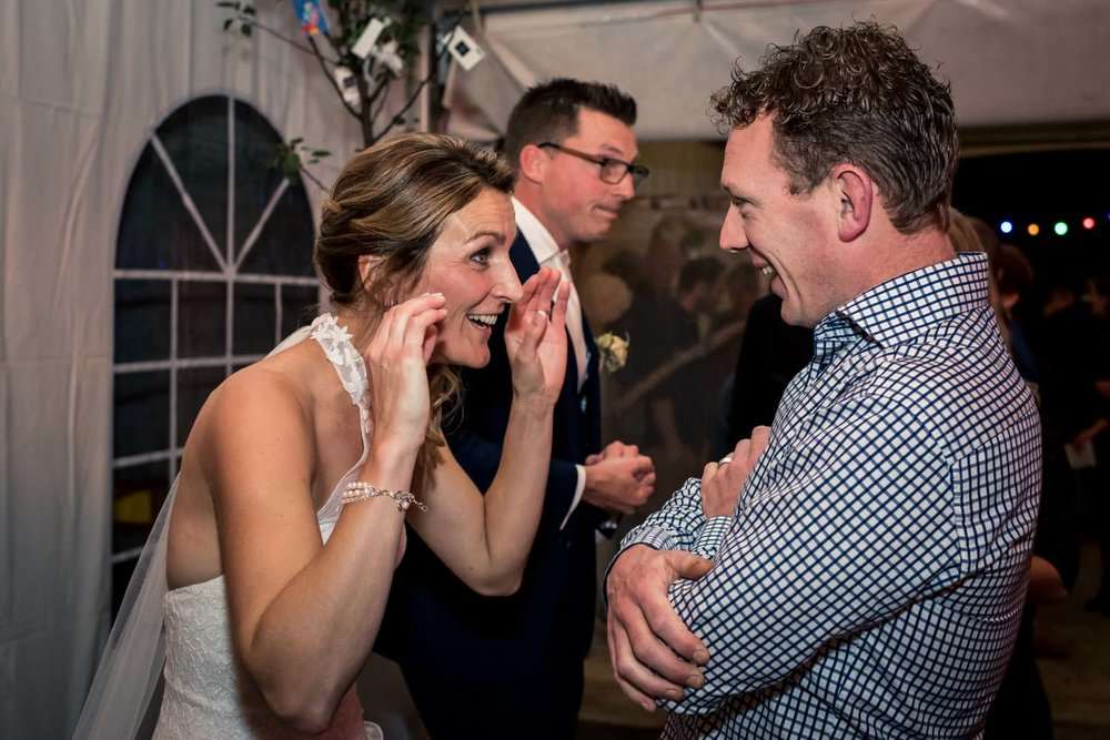 Spontaan moment tijden de felicitatie van de bruid met een gast.