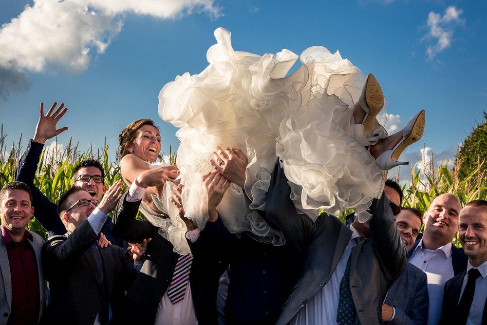 Huwelijksfotografie de groepsfoto van de bruid die omhoog gegooi
