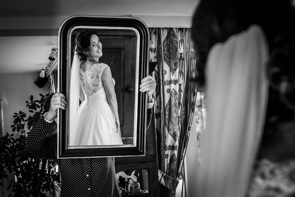 bruidsfotograaf maakt foto als de bruid in de spiegel kijkt