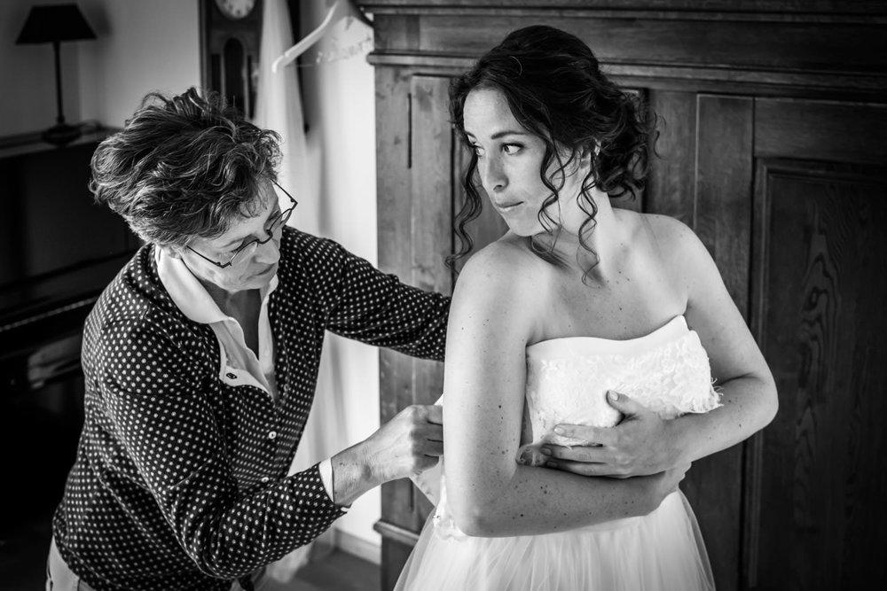 moeder helpt bruid bij aandoen van de jurk