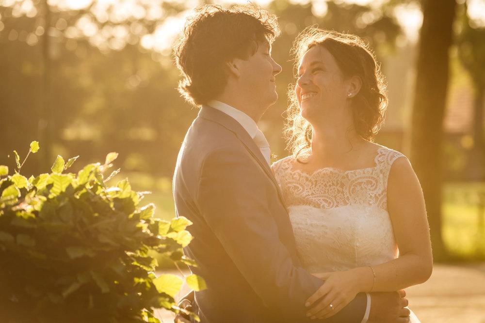 bruidspaar in het avondlicht met ondergaande zon