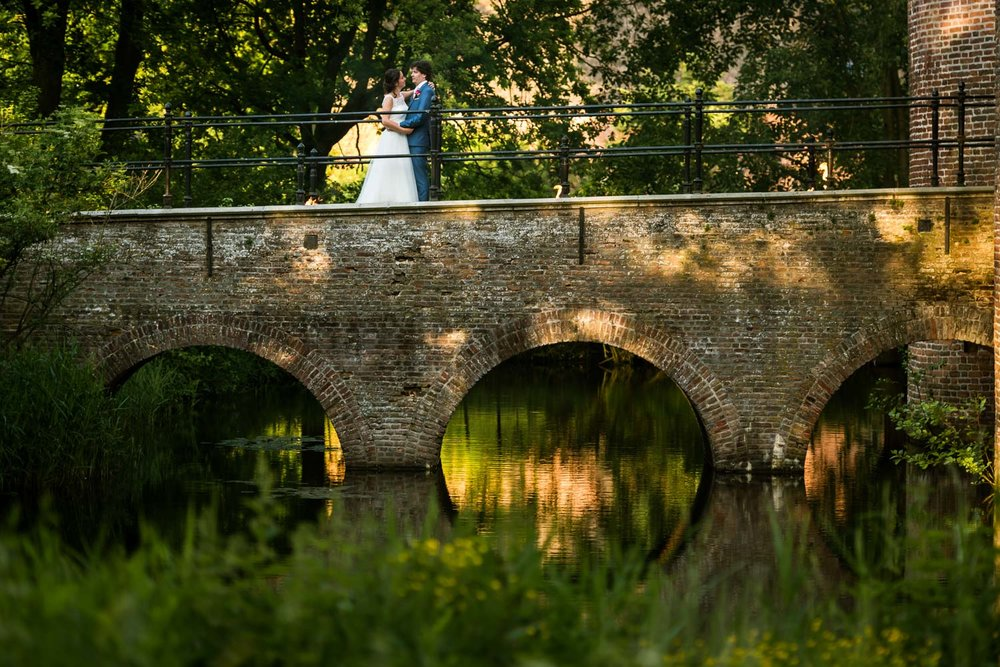 toegangsbrug op kasteel dussen met avondlicht en bruidspaar