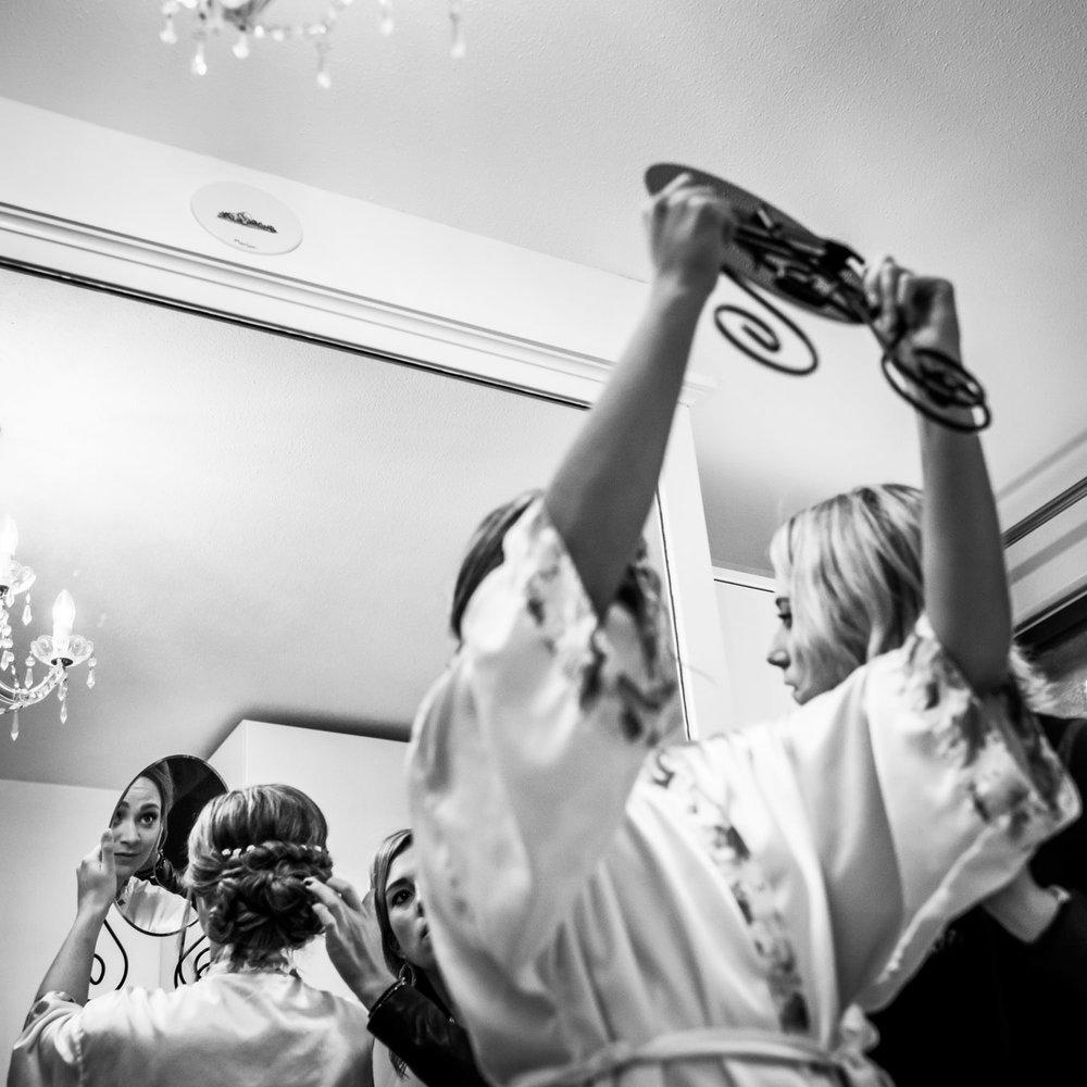 De bruid kijkt in de spiegel tijdens het aankleden, door trouwfo
