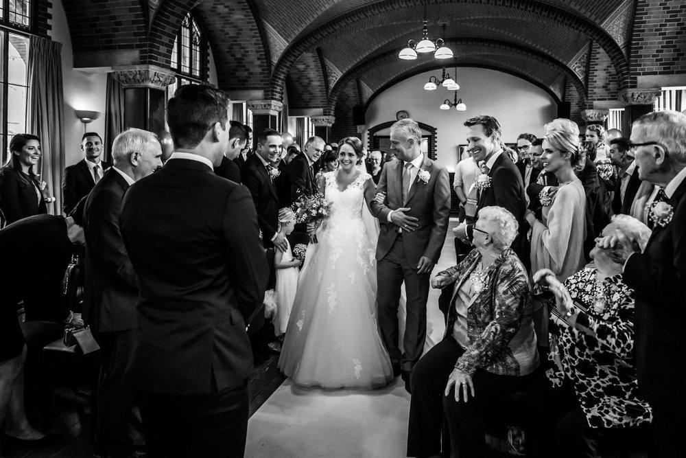 De bruid komt met haar vader binnen tijdens de ceremonie van een