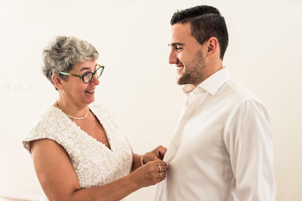De bruidegom wordt door zijn moeder geholpen bij het aankleden