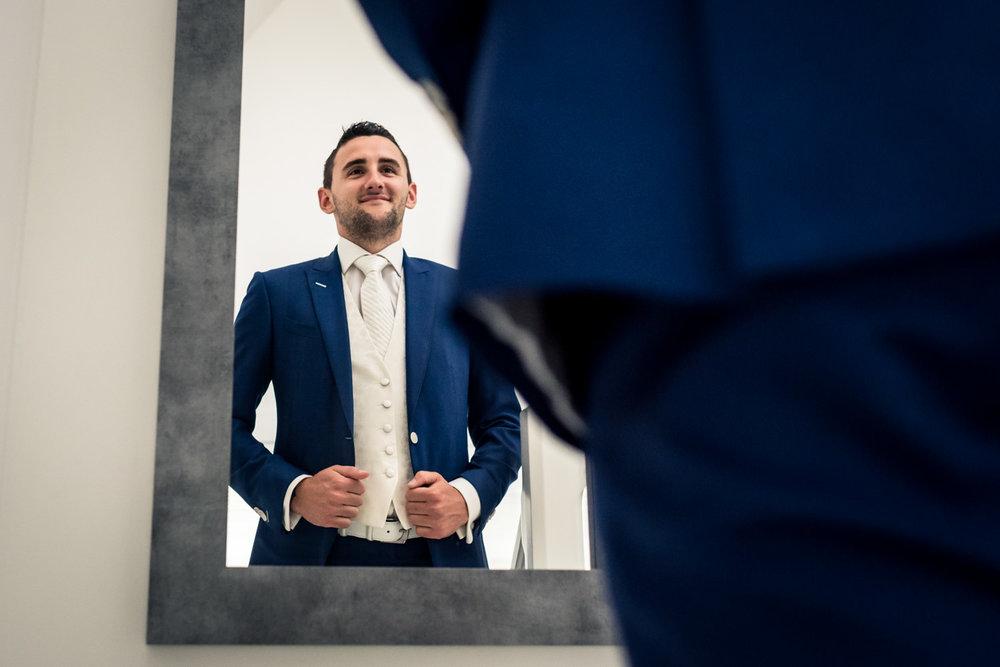 Bruidegom tijdens getting ready hij staat voor de spiegel