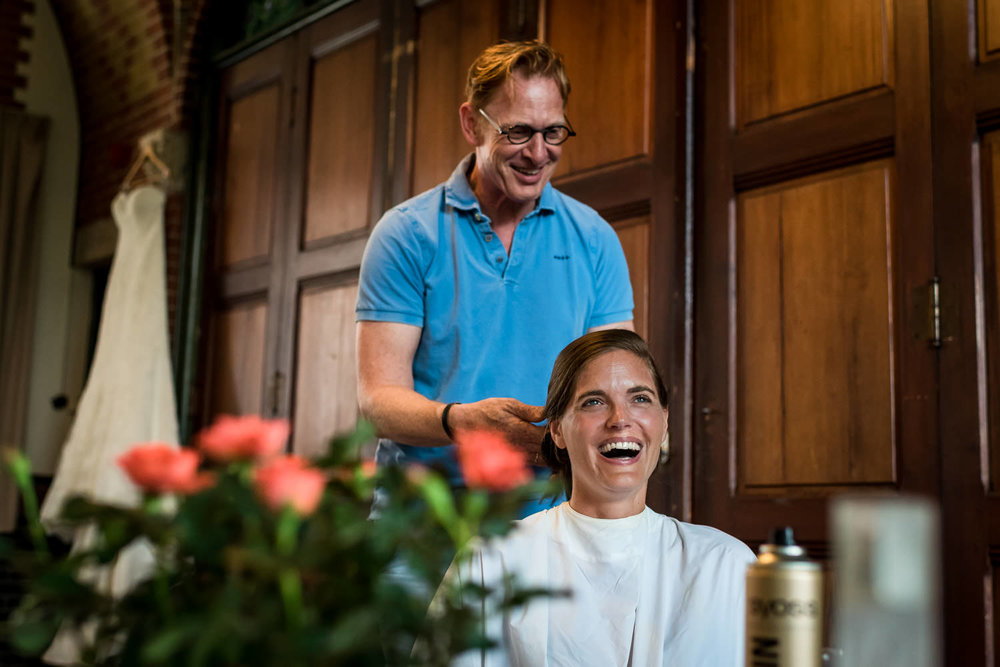 vrolijke bruid tijdens de make up en haar styling