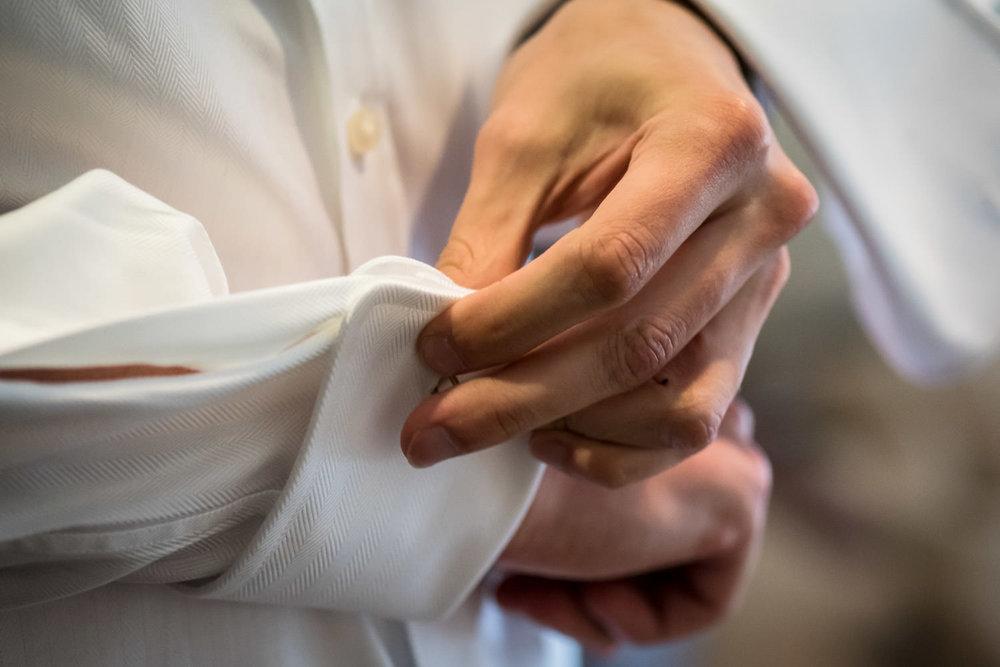 foto van het vastmaken van de manchetknopen door de bruidegom