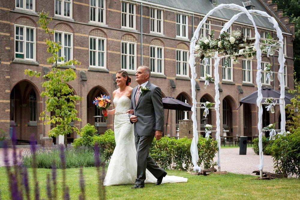 De bruid loopt met haar vader bij de aanvang van de ceremonie na