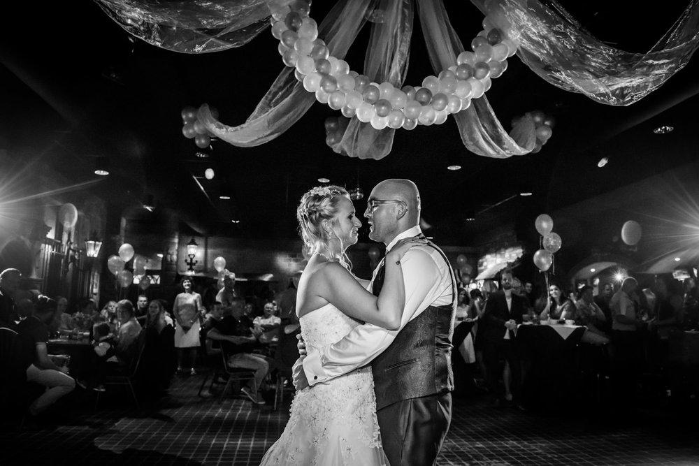 het bruidspaar tijdens de openingsdans, er hangen balonnen, brui
