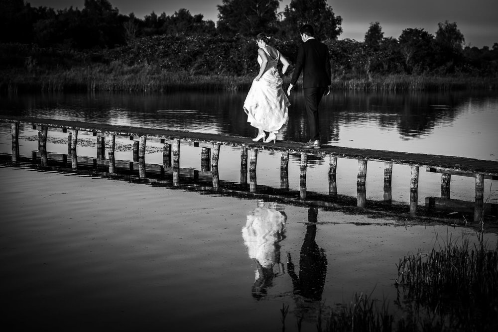 Super toffe bruidsfotografie, het bruidspaar loopt over het brug