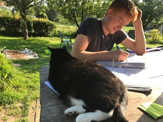 Ruben doing homework with the farm cat.jpg