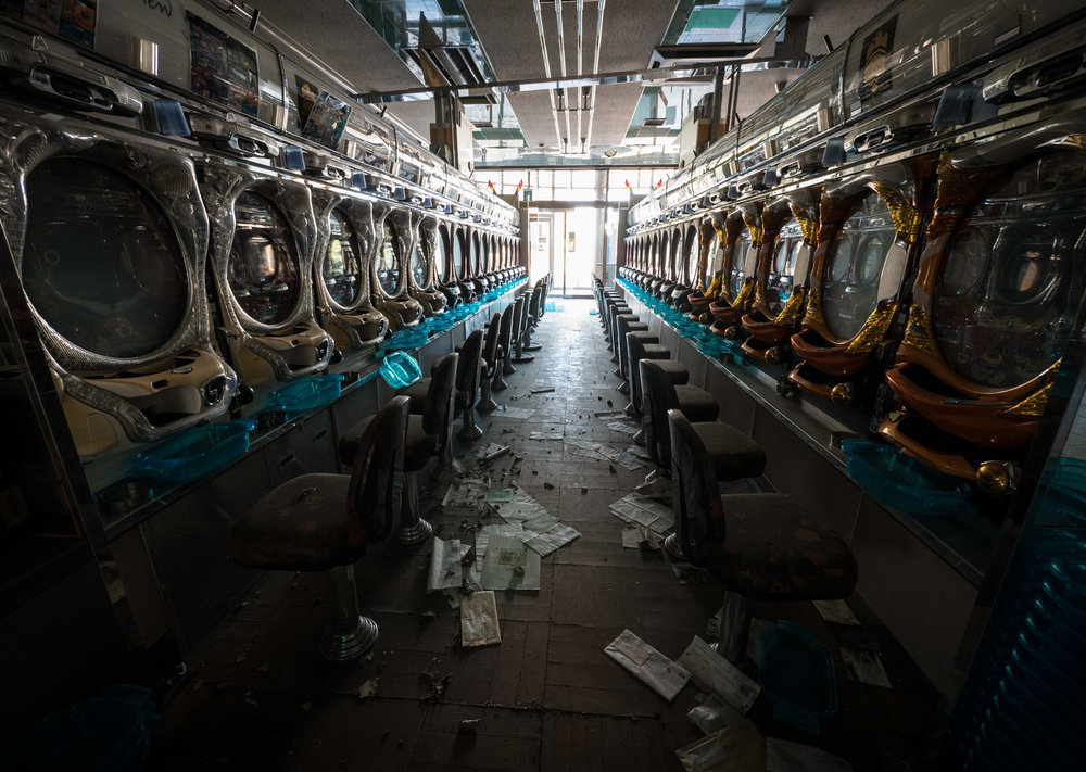 A view down an aisle inside the Pachinko hall. Some of the machines have been damaged but most look like they are in good condition.
