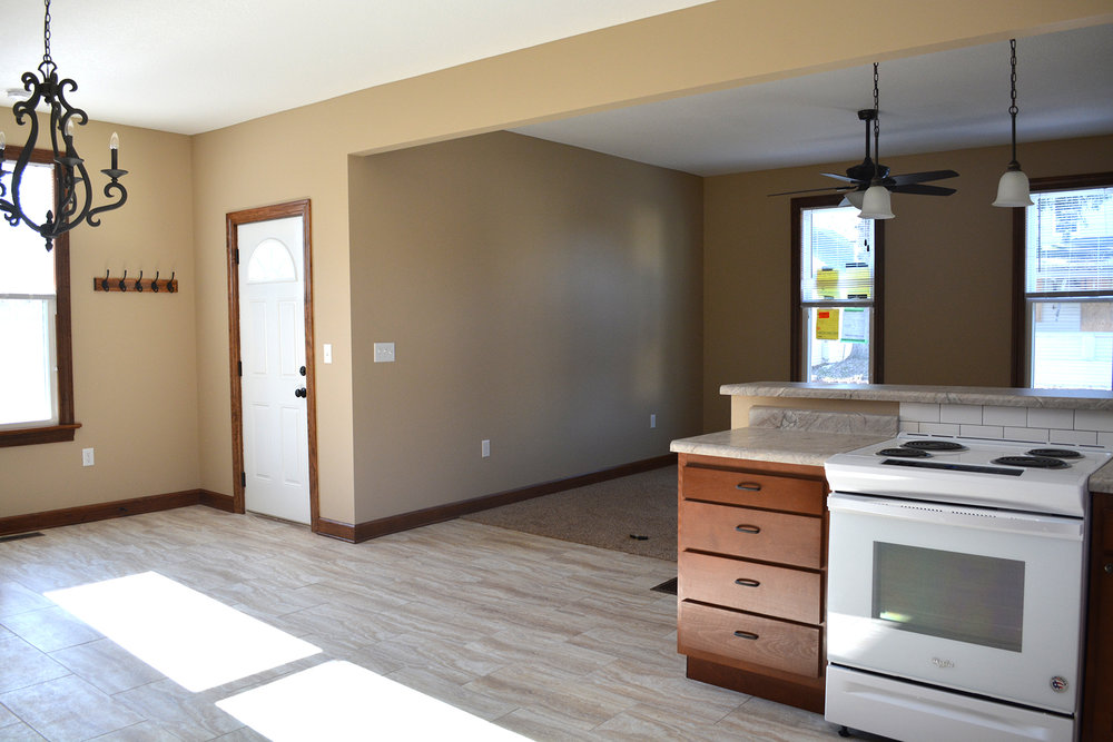 AFTER: The kitchen is now in the center of the house, open to the entry, dining, and living rooms.